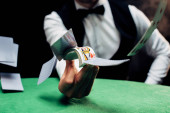 KYIV, UKRAINE - AUGUST 20, 2019: cropped view of croupier throwing in air playing cards near poker table on black