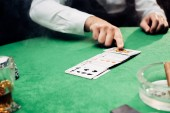 KYIV, UKRAINE - AUGUST 20, 2019: cropped view of croupier pointing with finger at playing cards on black