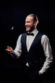 Fotografia felice uomo barbuto gettando in aria chip poker isolato sul nero