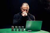 Kyiv, Ucraina - 20 agosto 2019: uomo che copre il volto durante lutilizzo di laptop vicino a chip di poker e carte da gioco sul nero con fumo