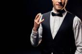 oříznutý pohled člověka na formální opotřebení držení pokeru čip izolovaný na černém