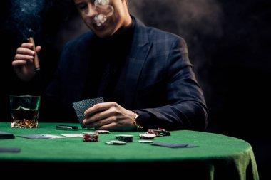 KYIV, UKRAINE - AUGUST 20, 2019: cropped view of man smoking cigar on black with smoke