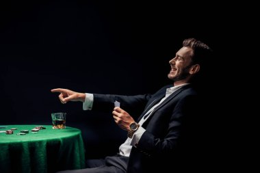 KYIV, UKRAINE - AUGUST 20, 2019: happy man pointing with finger and holding playing cards isolated on black