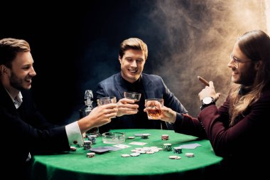 KYIV, UKRAINE - AUGUST 20, 2019: happy men holding glasses with alcohol near poker table on black with smoke