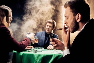 selective focus of handsome man smoking while playing poker on black with smoke