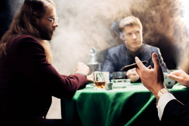 cropped view of man holding cigar while playing poker on black with smoke