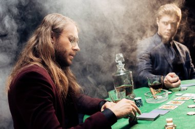 KYIV, UKRAINE - AUGUST 20, 2019: handsome men playing poker near poker table with poker chips and playing cards on black with smoke
