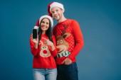 pár v Santa kloboucích a vánoční svetry ukazující na smartphone s prázdnou obrazovkou izolovanou na modré