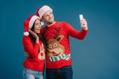 Aufgeregtes Paar in Weihnachtsmützen und Weihnachtspullis macht Selfie auf Smartphone