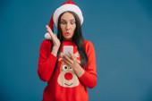 atraktivní překvapovaná žena v Santa klobouku a vánočním svetru pomocí smartphone izolovaného na modrém