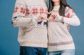 vista ritagliata di coppia in inverno maglioni mostrando segno cuore isolato sul blu