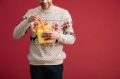 oříznutý pohled na šťastného muže otevírající vánoční dárek izolovaný na červenou