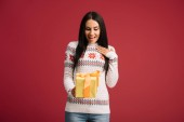überrascht Mädchen mit Weihnachtsgeschenk isoliert auf rot