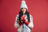 Frau im Winter Hut, Schal und Handschuhe halten Kaffee zu gehen, isoliert auf rot