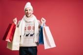 schöner lächelnder Mann in Winterkleidung mit Einkaufstaschen, isoliert auf rotem Grund