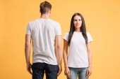 beautiful couple posing in white t-shirts, isolated on yellow