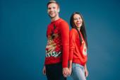 Lächelndes Paar in Weihnachtspullis, Händchen haltend auf blauem Grund