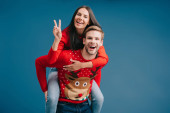 happy couple in christmas sweaters piggybacking and showing peace symbol isolated on blue