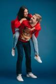 szép pár karácsonyi pulóverek piggybacking elszigetelt kék