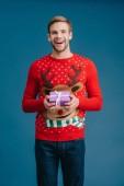 schöner Mann im Pullover hält Weihnachtsgeschenkschachtel isoliert auf blauem Grund