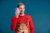 mosolyogva fiatalember pulóvert gazdaságban karácsonyi ajándékot elszigetelt sárga