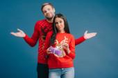 barátnőjét gazdaság karácsonyi ajándékot, barát állt mögötte a vállrándítással gesztus elszigetelt kék