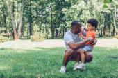 roztomilý africký americký chlapec sedí na koleni šťastný otec v parku
