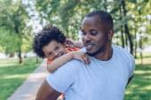 pohledný africký Američan muž piggybacking veselý syn v parku