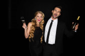 Fröhliches Paar feiert mit Champagner auf Schwarz