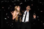 schönes fröhliches Paar feiert mit Champagner auf Schwarz mit goldenem Konfetti