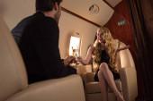 veselý pár pití šampaňského při cestování v letadle