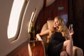 smiling glamorous woman with champagne sitting in plane