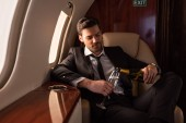 handsome man in suit pouring champagne into glass in plane