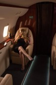 happy glamorous woman with champagne sitting in plane