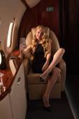 Fotografie Lächelnde Frau macht Selfie auf Smartphone mit Champagner im Flugzeug
