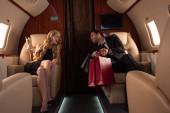 veselý elegantní pár pití šampaňské při cestování v letadle