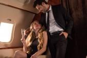 šťastný elegantní pár pití šampaňské při cestování v letadle