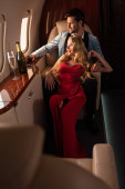 elegant sexy couple with champagne sitting in airplane