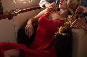 cropped view of elegant sexy couple sitting in airplane