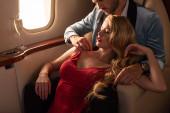 schöne elegante sexy Paar mit Champagner sitzen im Flugzeug