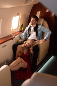 beautiful sensual couple with champagne sitting in airplane