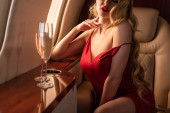 cropped view of sexy glamorous woman with champagne sitting in plane