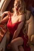 krásná sexy žena v červených šatech sedí v letadle