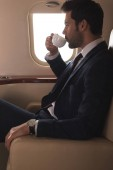 handsome businessman in suit drinking coffee in airplane during business trip