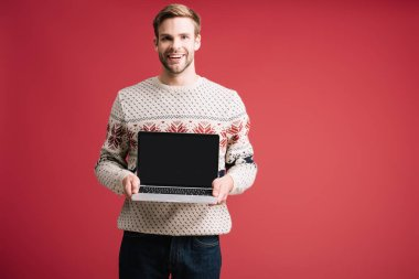 Handsome smiling man showing laptop with blank screen isolated on red stock vector