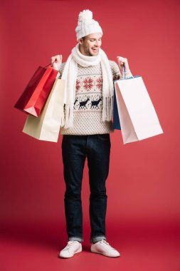 kış eşarp neşeli adam, şapka ve kazak tutan alışveriş çantaları, kırmızı izole