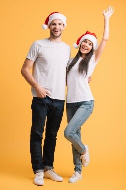Excited couple in santa hats having fun on yellow stock vector