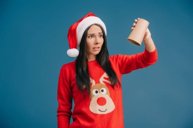 Upset woman in santa hat holding empty cup of coffee, isolated on blue stock vector
