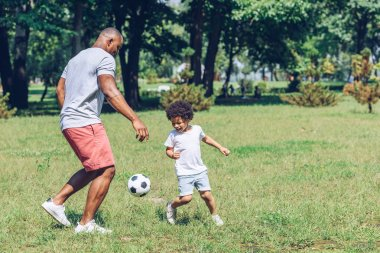 young african american father playing football with cute son in park