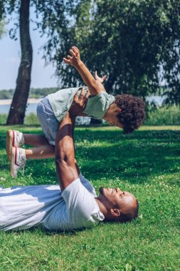 happy african american father and son having fun on lawn in park
